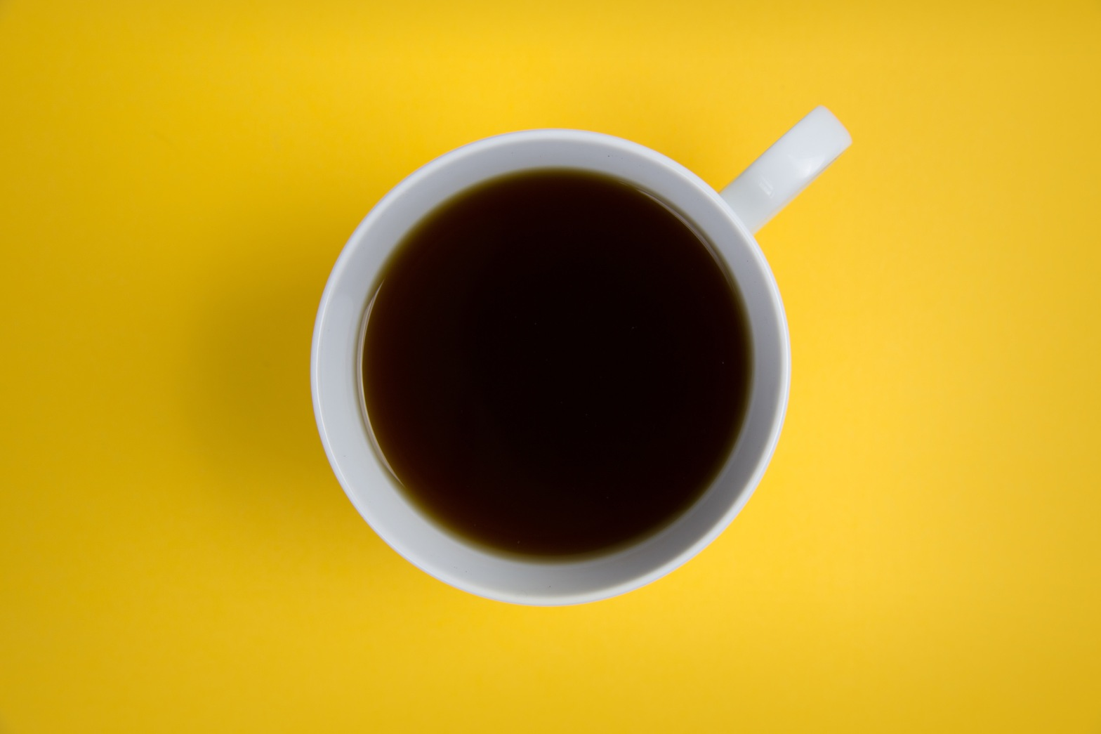 Top down view of coffee mug on a yellow surface