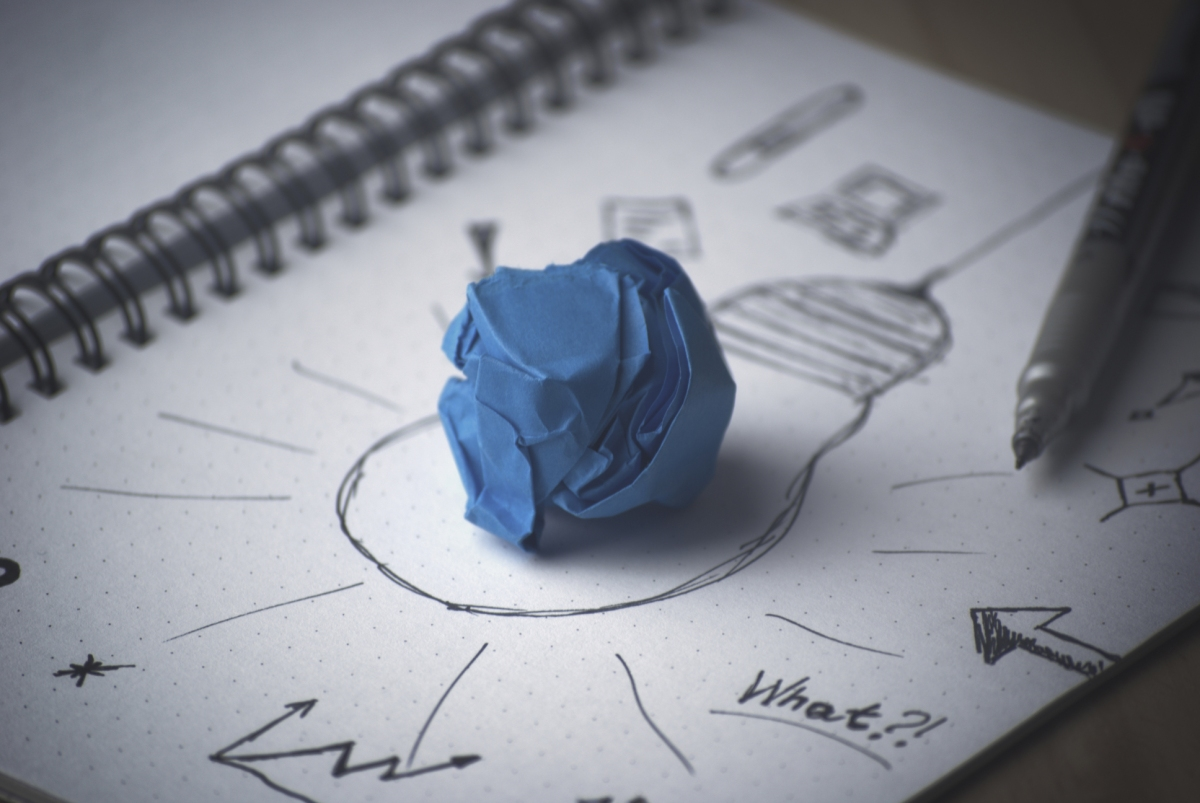 Lightbulb drawing on white paper with blue paper ball