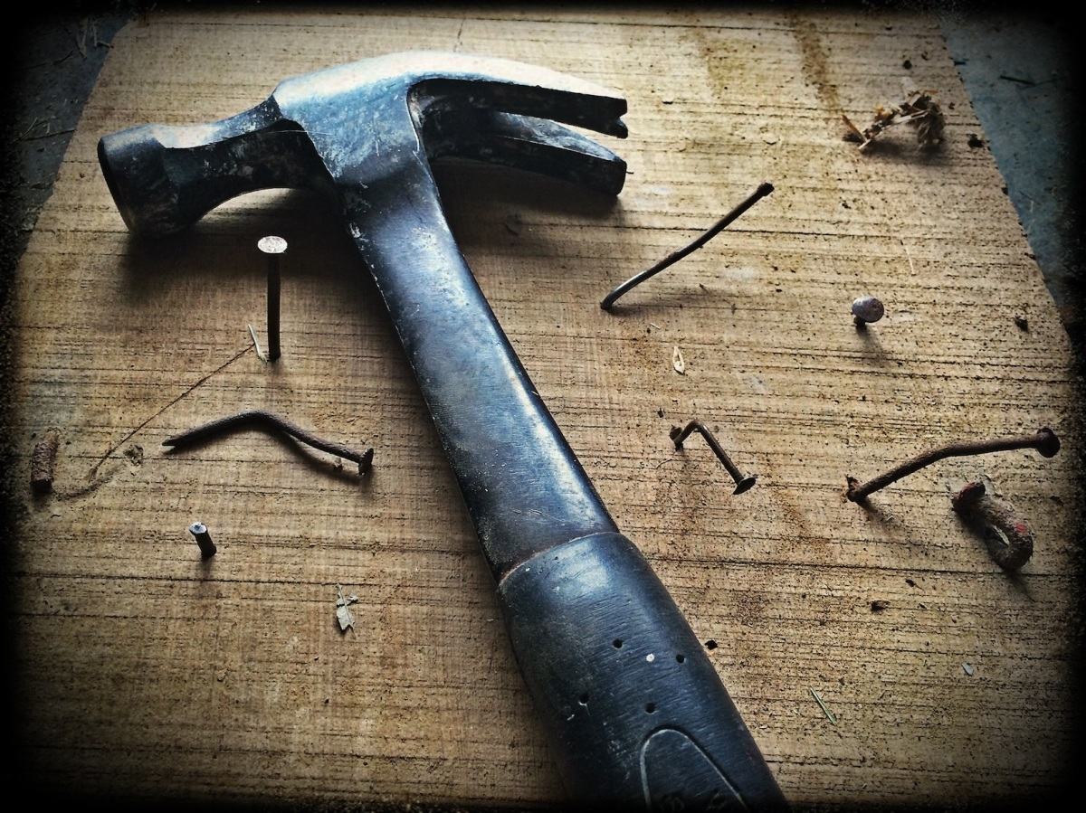 Hammer and bent nails on a wood block