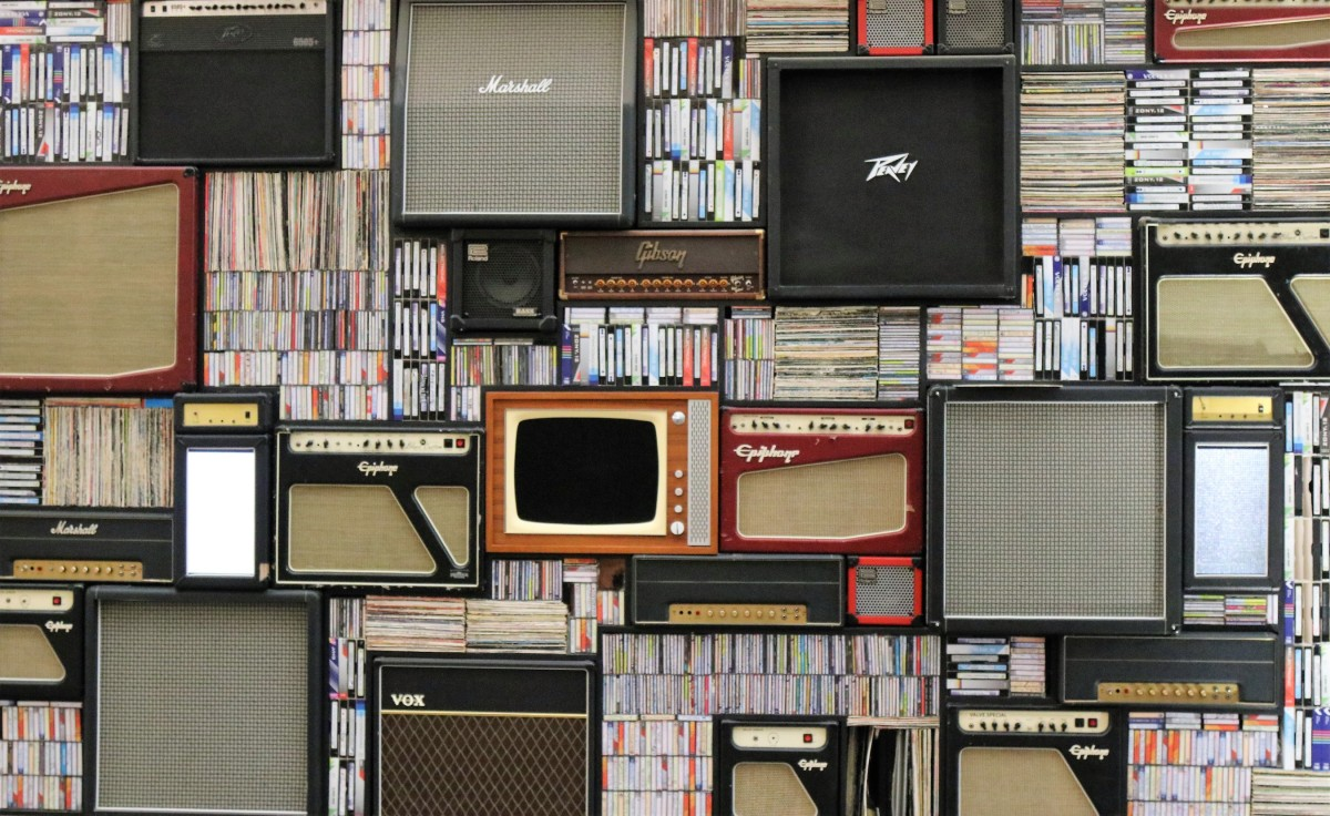 Assorted music amps, records, tapes, books, and televisions on a wall