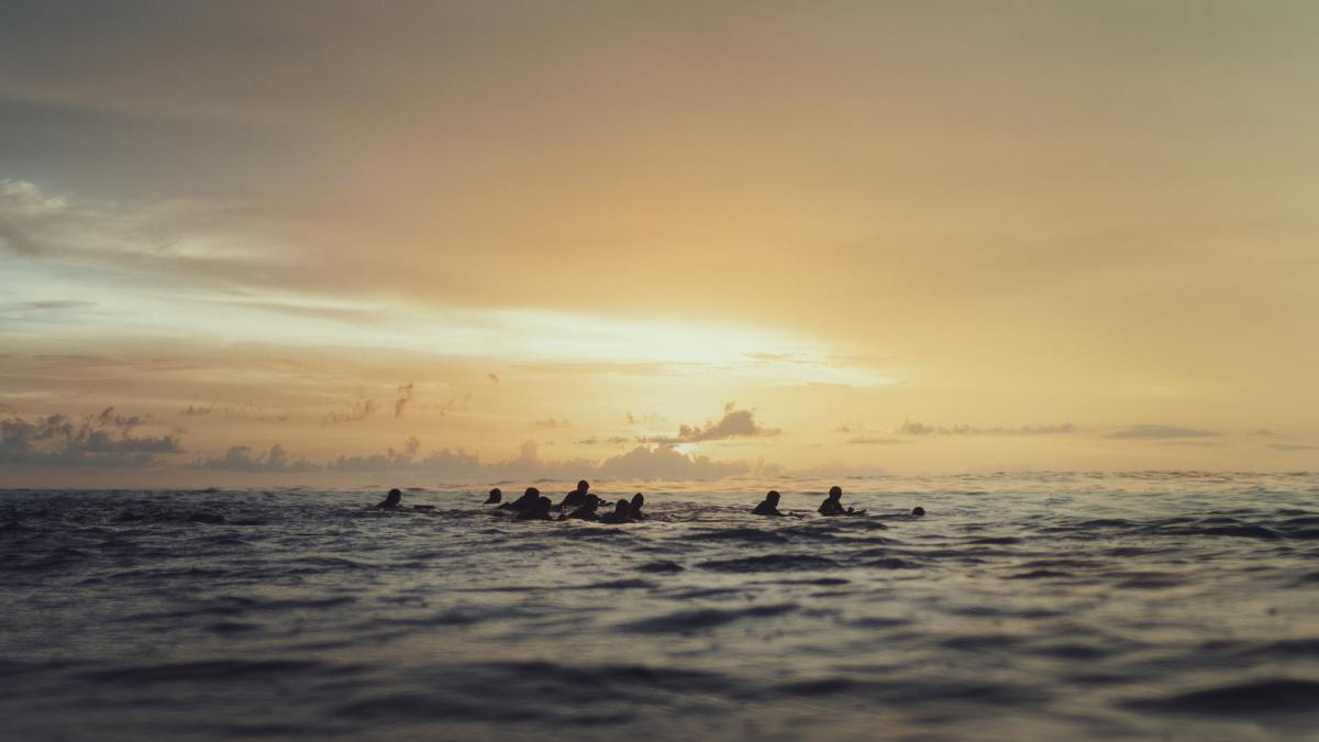 A group of people floating in open water at dusk