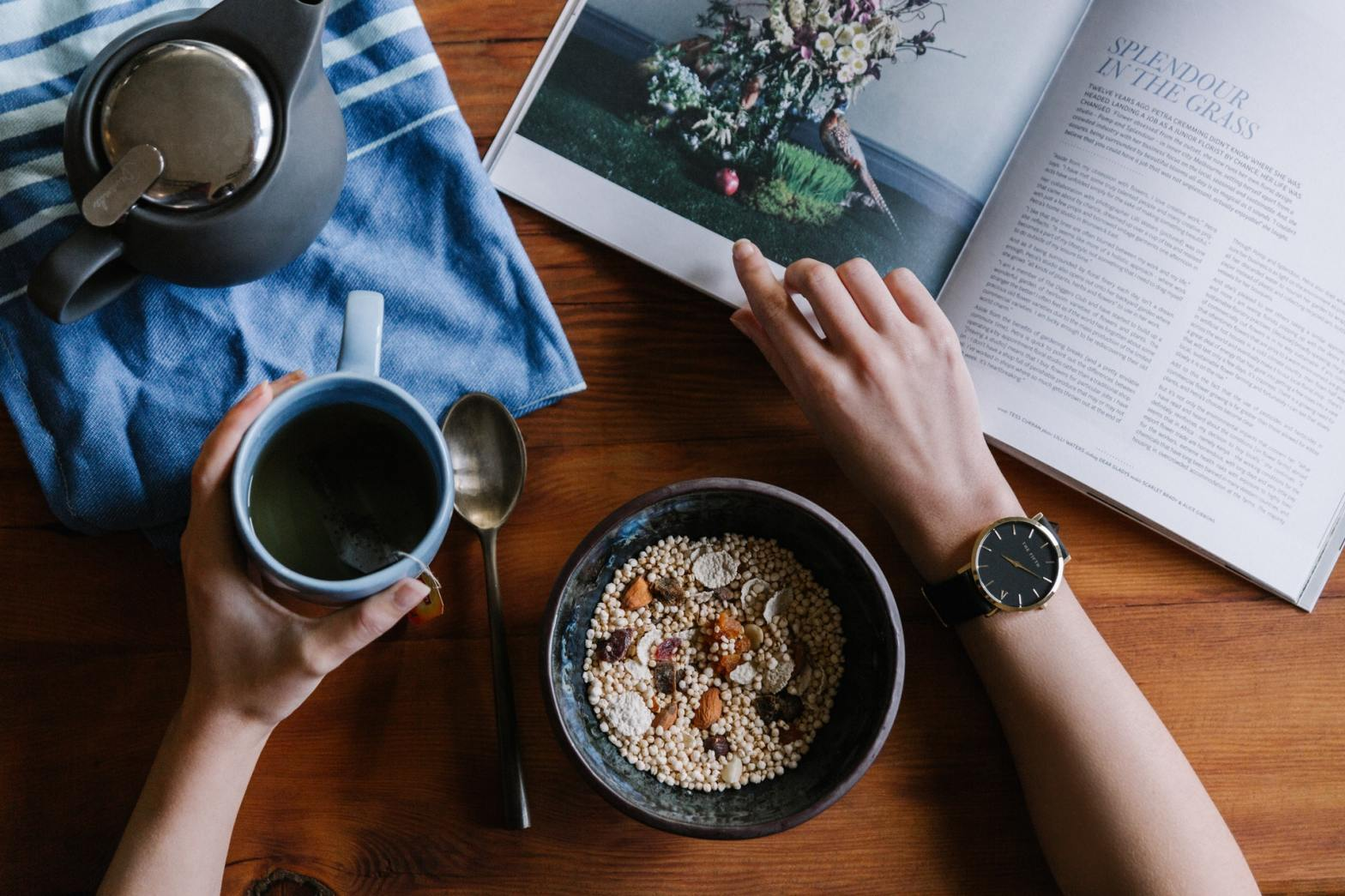 Person sitting at a table reading a book with a bowl of cereal and cup of tea